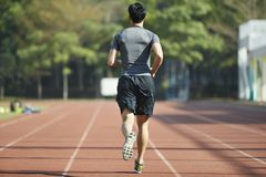 Young asian male athlete running on track. Young asian man male athlete running training exercising on track, rear view Royalty Free Stock Photos
