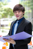 Young Asian male business executive holding file Stock Photography