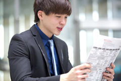 Young Asian male business executive reading newspaper Royalty Free Stock Photo