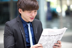 Young Asian male business executive reading newspaper Royalty Free Stock Photos