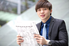 Young Asian male business executive reading newspaper Royalty Free Stock Images