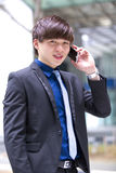 Young Asian male business executive using smart phone Royalty Free Stock Photos