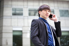 Young Asian male business executive using smart phone Royalty Free Stock Photo
