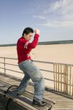 Young asian male dancing by the beach. Young asian male dancing to his MP3 player on a bench next to the seaside Royalty Free Stock Photo