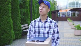 Young asian male delivery man in cap with box in hand stock video