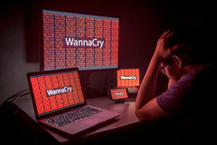 Young Asian male frustrated by WannaCry ransomware attack. Young Asian male frustrated, confused and headache by WannaCry ransomware attack on desktop screen Royalty Free Stock Photos