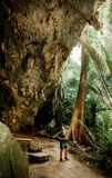 Young asian male photographer with casual cloth in forest cave t stock photo