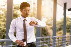 Young asian male standing checking time and holding coffee cup w. Ith confident looking at watches on hand at outside company Royalty Free Stock Photos
