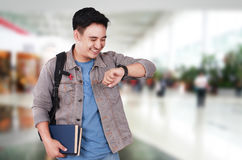 Young Asian Male Student Looking at His Watch. Time concept, photo image portrait of a successful cute young Asian male student smiling and looking at his Royalty Free Stock Photos