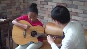 Young Asian male teacher giving a guitar lesson and teaching how to play guitar to African American girl