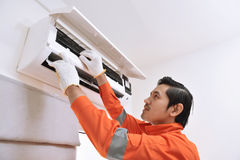 Young asian male technician repairing air conditioner. At home Stock Photos
