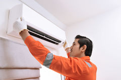 Young asian male technician repairing air conditioner. At home Stock Photo