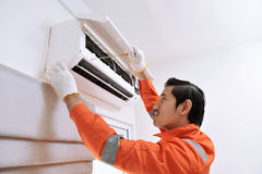 Young asian male technician repairing air conditioner with. Screwdriver at home Royalty Free Stock Image