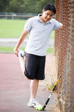 Young asian male tennis player. A young asian male stretching before playing tennis Stock Photo