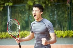 Young asian male tennis player celebrating stock image