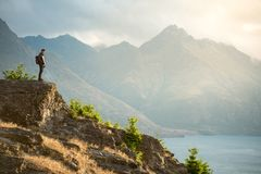 Young Asian male traveler with mountain scenery in Queenstown. Young Asian male traveler standing on the edge of vista lookout with mountain scenery and Lake Royalty Free Stock Photos