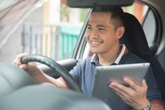Male using tablet pc. Young asian male using tablet pc while driving his car Royalty Free Stock Images