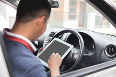 Male using tablet pc. Young asian male using tablet pc while driving his car Stock Images
