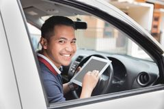 Male using tablet pc. Young asian male using tablet pc while driving his car Royalty Free Stock Photography