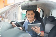 Male using tablet pc. Young asian male using tablet pc while driving his car Stock Image