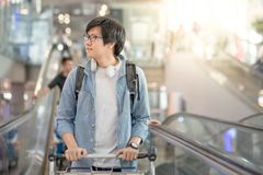 Young Asian man with airport trolley on escalator Royalty Free Stock Photography