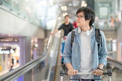 Young Asian man with airport trolley on escalator Stock Photos