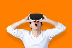 Young Asian Man Amazed By Virtual Reality. A young asian man against an orange background in casual white outfit wearing VR glasses looking up and feeling royalty free stock photography