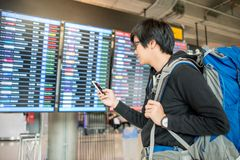 Young asian man with backpack bag checking for his flight. From the flight information board and holding smartphone at airport terminal royalty free stock photos