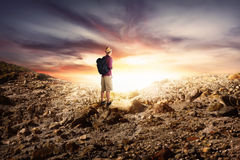 Young asian man with backpack hiking in rocky mountains Royalty Free Stock Photography