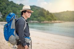 Young Asian man backpacker standing on the beach. Summer holiday vacation and travel tropical island concepts Royalty Free Stock Photo