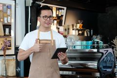 Young asian man, barista, using tablet at cafe counter background, food and drink concept stock photography