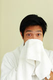 Young asian man in bathrobe wiping face Royalty Free Stock Photography