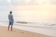 Young Asian man on the beach looking sunset. Young Asian man with jean shirt and hat standing on the beach and looking beautiful sunset, vacation time and summer Stock Photos