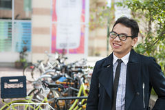 Young asian man with bicycle. Young smiling asian business man or student standing in front of bicycle parking rack on city street, with copy space Royalty Free Stock Images