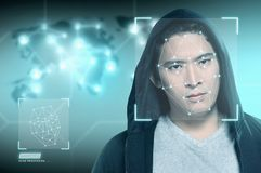Young asian man in black hoodie using face recognition. Over digital world map background. Modern technology concept royalty free stock photos