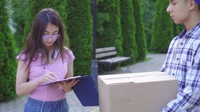 Young asian man with a box in his hands delivers an order to a young asian woman stock footage