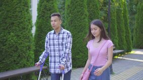 Young asian man with broken leg on crutches communicates with young asian woman in park stock footage
