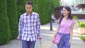Young asian man with broken leg on crutches communicates with young asian woman in park close up slow mo stock footage