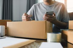Young asian man business owner hands writing address on cardboard box at workplace or home office.  royalty free stock photo