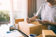 Young asian man business owner hands writing address on cardboard box at workplace or home office royalty free stock image
