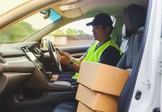 A young Asian man in a car with a cardboard box ready for delive Stock Image