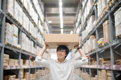 Young Asian man carry paper box over head in warehouse stock image