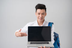 Young asian man in casual clothes holding and showing screen of. Laptop Royalty Free Stock Photo