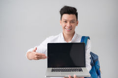 Young asian man in casual clothes holding and showing screen of stock photos