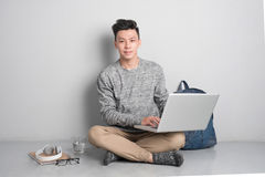 Young asian man in casual clothes is using a laptop, smiling whi Stock Photo