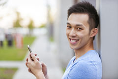 Young asian man with cellphone Royalty Free Stock Photo