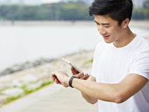 Young asian man checking cellphone and watch before exercise royalty free stock photography