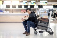 Young Asian man sitting on trolley in airport terminal Stock Photos
