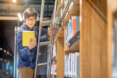 Young Asian man choosing book in library. Young Asian man choosing book in bookshelf using ladder in library, male student dressed in casual style. high school Royalty Free Stock Photos