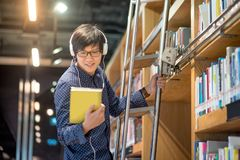 Young Asian man choosing book in library. Young Asian man choosing book in bookshelf using ladder in library, male student dressed in casual style. high school Stock Image